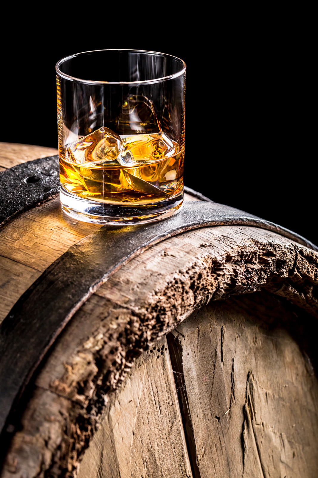 Whiskey glass and old wooden barrel.